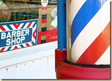 A US barber pole in front of a barber shop