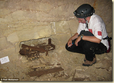 An Egyptologist examines a wood coffin containing the remains of a mummified dog